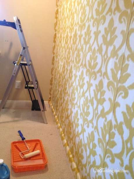 4. Antes de terminar de seguir o nosso tutorial de como colar tecido na parede, é assim que vai ficar, com sobras dos lados