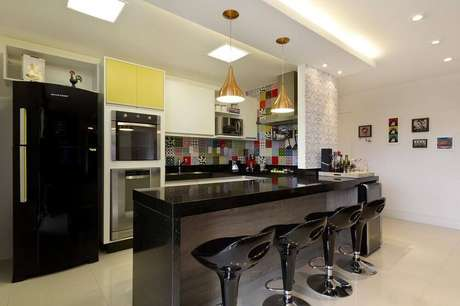 32. Cozinha americana com bancada e geladeira preta
