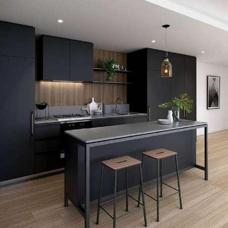 17. Decoração com armário de cozinha preto e parede revestida com madeira.