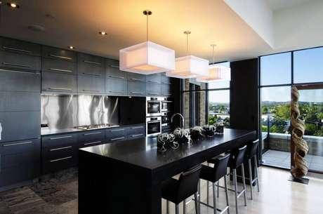 4. Cozinha planejada preta bem iluminada com grandes janelas e pendentes brancos