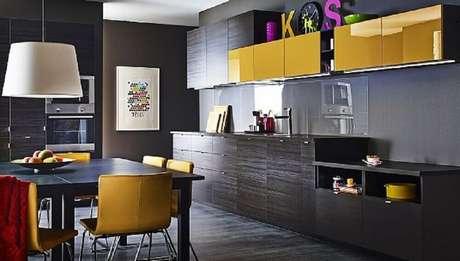 13. Cozinha preta e amarela com pendente branco e armário de cozinha preto