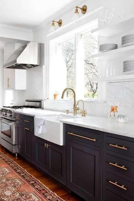 10. Sofisticada cozinha preta e branca com armário de cozinha preto e detalhes em dourado.