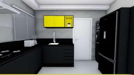 14. Cozinha preta e amarela com armário de cozinha preto.