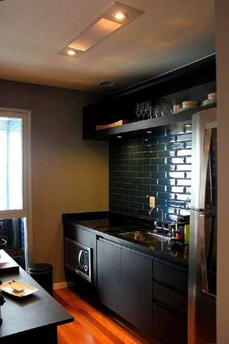 52. Cozinha planejada preta com ladrilho hidráulico e piso de madeira