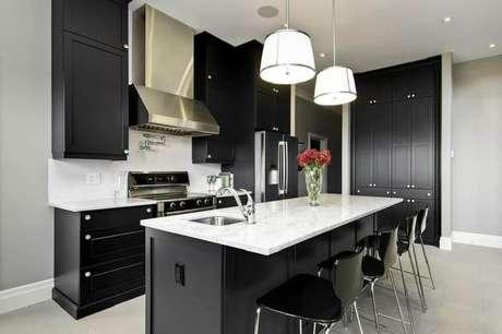 6. Cozinha decorada com pendentes sobre a ilha e com armário de cozinha preto planejado e com bancada branca.