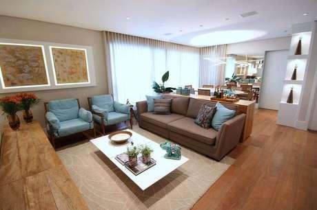 37. Decoração de sala com sofá marrom e almofadas azuis e estampadas