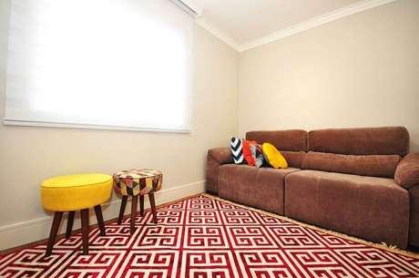 24. Decoração de sofá marrom com almofadas coloridas e tapete vermelho