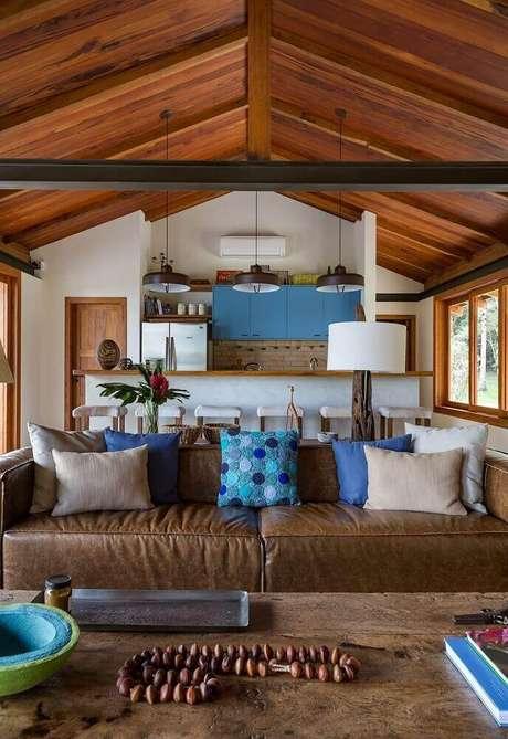 40. Decoração de sala com sofá marrom com almofadas em tons de cinza e azul