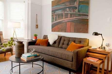 8. O laranja é um tom que contrasta bastante com o sofá marrom com almofadas