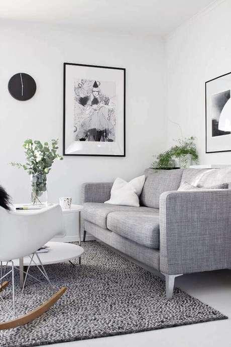 1. Decoração de sala com sofá cinza e quadro na parede.