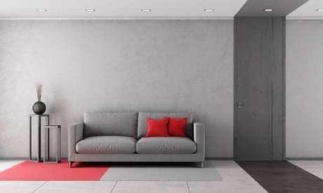 2. Decoração de sala com parede cinza com tonalidades diferentes e almofadas vermelhas.
