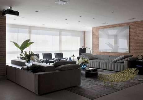 37. A parede de tijolinho trás um toque de conforto para a sala com sofá cinza