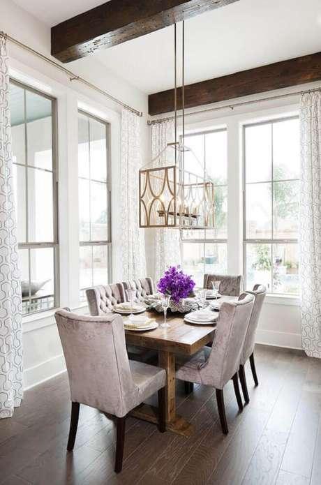 12. Casa de rico com mesa de madeira e lustre com design moderno.