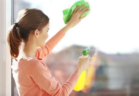 Mulher limpando janela: utilize uma solução de água com saquinhos de chá usados