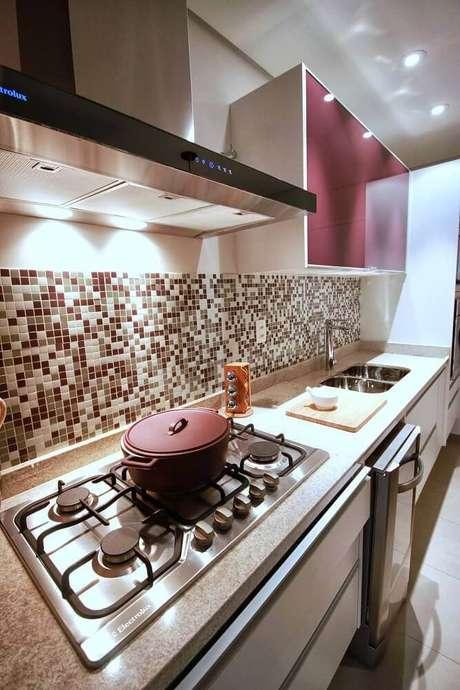37. Cozinha com coifa de parede e revestimento de pastilhas