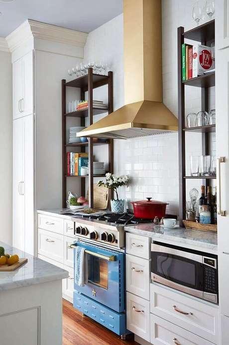 11. A coifa pode se tornar o grande destaque na cozinha com coifa de parede, como essa cozinha que recebeu uma linda coifa dourada.