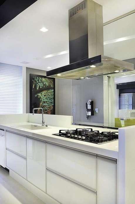 3. Cozinha planejada com coifa de alumínio que possui iluminação embutida