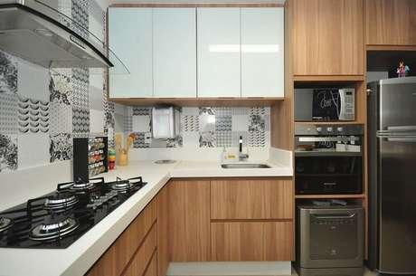 15. Cozinha planejada com coifa de vidro e azulejo decorativo nas paredes