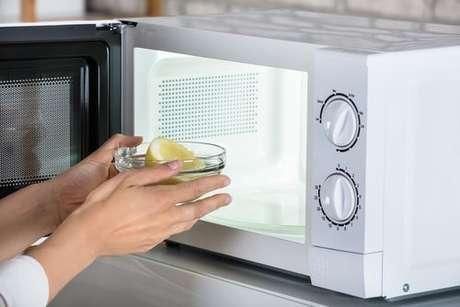 Recipiente com água e limão sendo colocado no micro-ondas