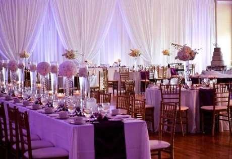 54. Decoração de casamento com arranjos de flores e suportes de vidro para mesa