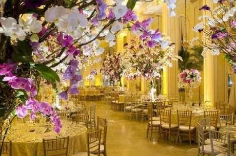 23. Essa decoração de casamento recebeu muitas flores e tons de dourado