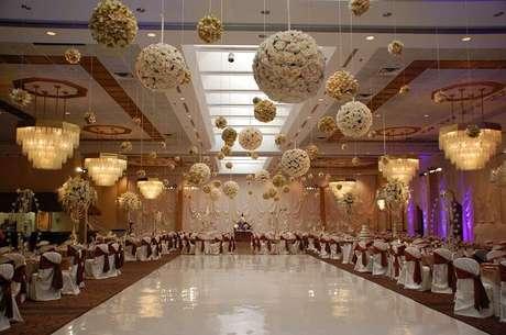 14. Decoração de festa de casamento com lustres e arranjos de flores no teto