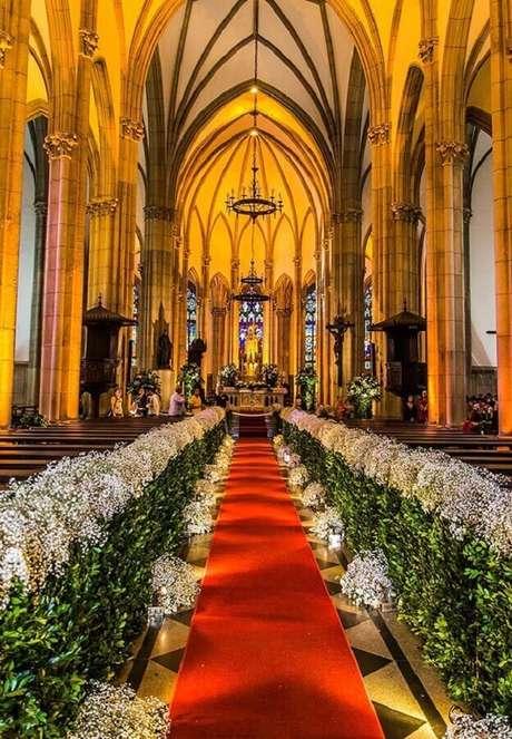3. Tradicional decoração de igreja para casamento em tons de branco e verde com o tapete vermelho.