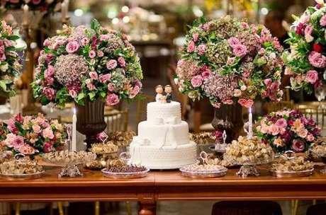 21. Decoração de mesa de casamento bem clássica com muitas flores e bolo branco