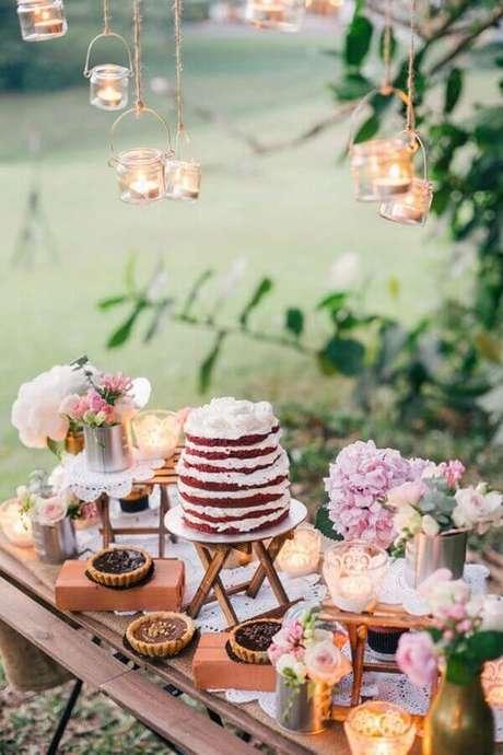 40. Decoração de mesa de casamento com bolo red velvet e luminárias suspensas