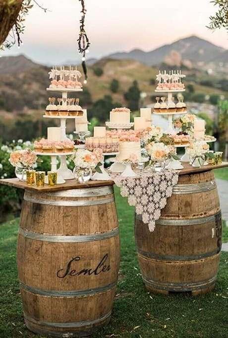 9. Decoração de mesa de casamento no campo com suporte de barris e detalhes delicados.