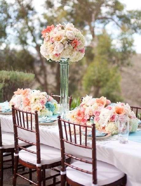 12. Decoração de festa de casamento com arranjos de flores em suportes altos