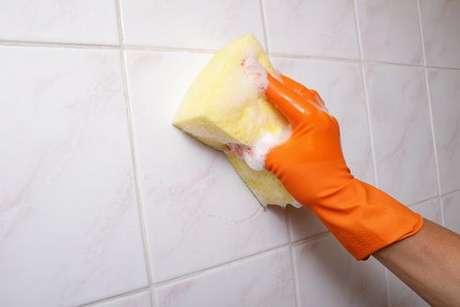 Azulejo engordurado sendo limpo com esponja