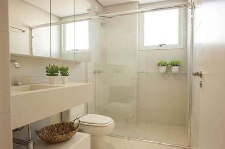 3. Modelo de banheiro simples com cores claras e pequenos vasos com plantas