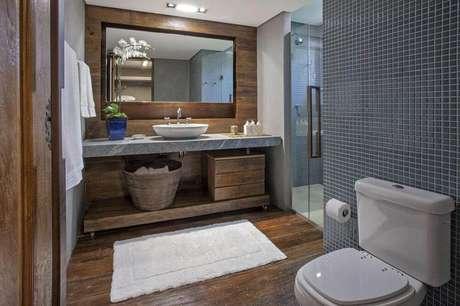 22. Esse modelo de banheiro com pastilha recebeu bastante toque de madeira para trazer sensação de conforto no ambiente