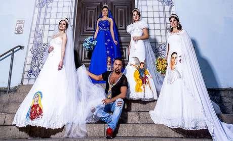 O estilista com modelos usando os vestidos com bordados de santos.