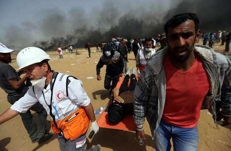 Resultado de imagem para Manifestante ferido é carregado durante confronto com soldados israelenses na fronteira entre Israel e Gaza