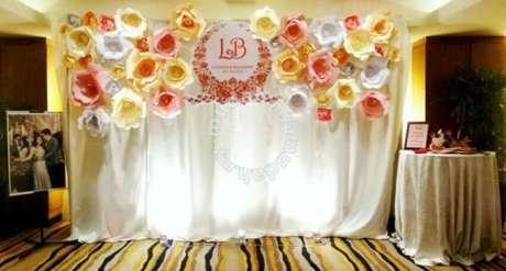 25. Decoração com flores de papel em mural para fotos