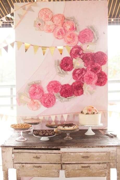 11. Mesa de doces com fundo com flores de papel rosa