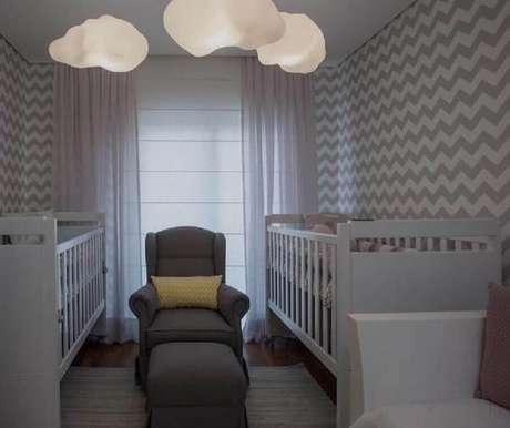 20. Decoração de quarto de bebê gêmeos com papel de parede zigue zague e luminárias em formato de nuvem
