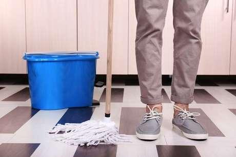 Pessoa tentando limpar o chão da cozinha