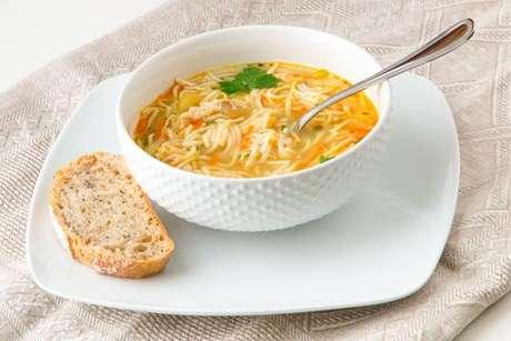 Sopa de macarrão servida com uma fatia de pão integral