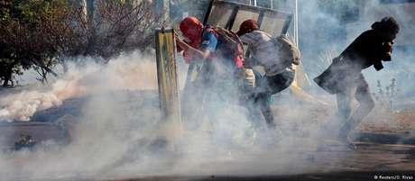Manifestantes em meio a nuvem de gás lacrimogêneo em Manágua