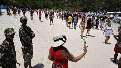 Guardas monitoram turistas em Maya Beach, na Tailândia, antes do banimento