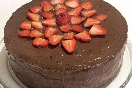 Bolo de chocolate com cobertura e decorado com morangos