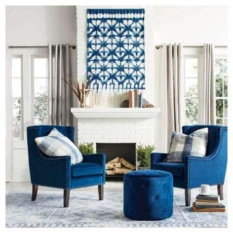 35. Sala com decoração clássica em tons de azul e branco onde o puff combina com as poltronas