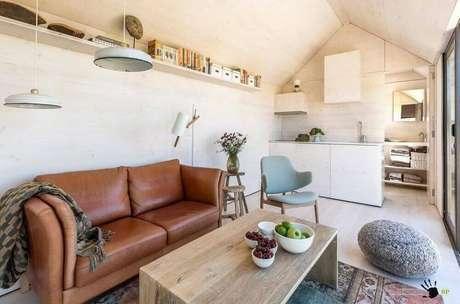 11. Decoração clean e delicada com com puff para sala pequena e sofá de couro