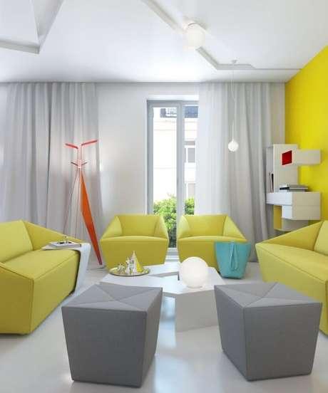14. Sala com decoração moderna em tons de amarelo e cinza e com puff quadrado