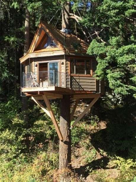 24. Casa na árvore com pilares de madeira na estrutura