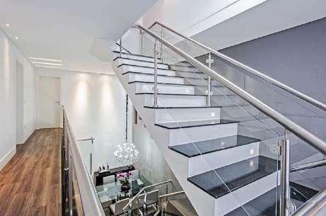 29. Para manter a decoração clean escolha um modelo de escada com detalhes em vidro e inox