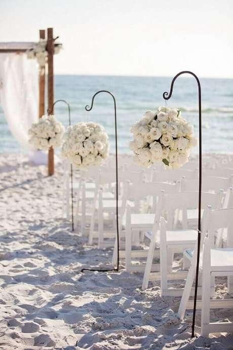 19. Linda decoração com arranjos de rosas brancas para a cerimônia de noivado na praia